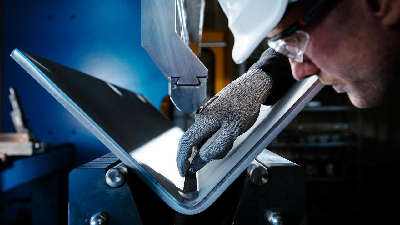 Personne inspectant le pliage d'une plaque d'acier Strenx®.