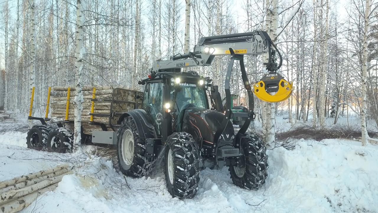 Un trattore con gru in Strenx® che raccoglie legname in una foresta invernale.
