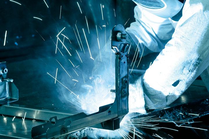 En operatör svetsar höghållfast Strenx®-stål i verkstaden.